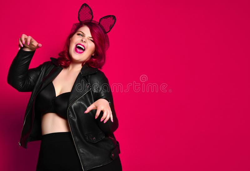 Cute sexy plus size brunette with black bunny ears in leather jacket and underwear posing on red background stock photos