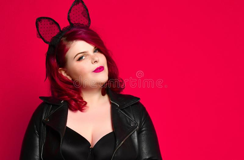 Cute sexy plus size brunette with black bunny ears in leather jacket and underwear posing on red background.  royalty free stock photography