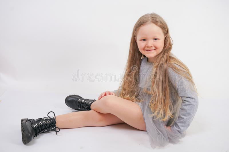 Cute shy caucasian baby girl in grey dress and alternative big boots sitting and posing on white background in Studio alone stock image