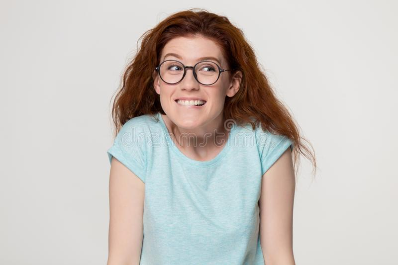 Cute shy redhead girl in glasses biting lips feeling embarrassed stock photo