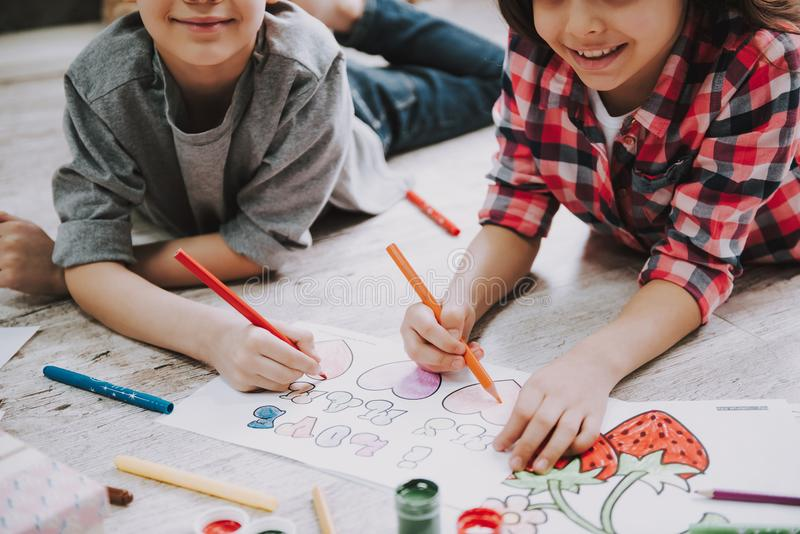 Cute Siblings Drawing with Markers Laying at Floor royalty free stock image