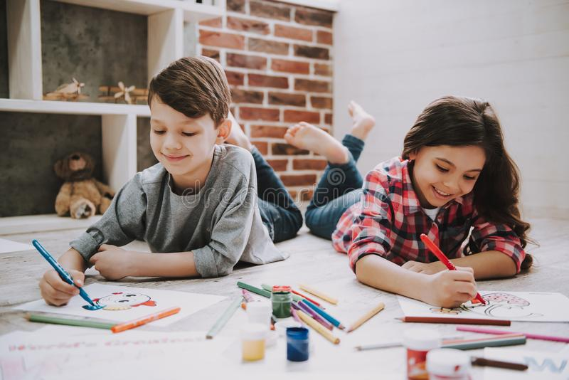 Cute Siblings Drawing Pictures Laying at Floor stock photos