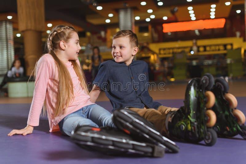 cute siblings in roller skates resting after skating royalty free stock photos