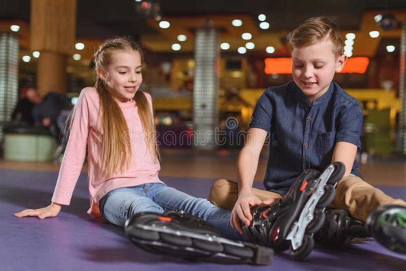 cute siblings in roller skates resting after skating stock photography