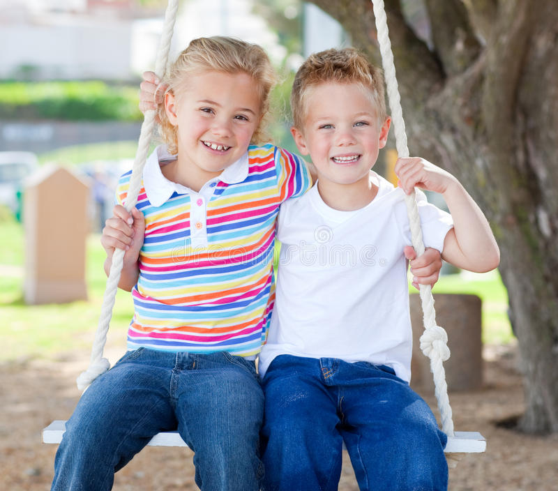Cute siblings swinging stock image