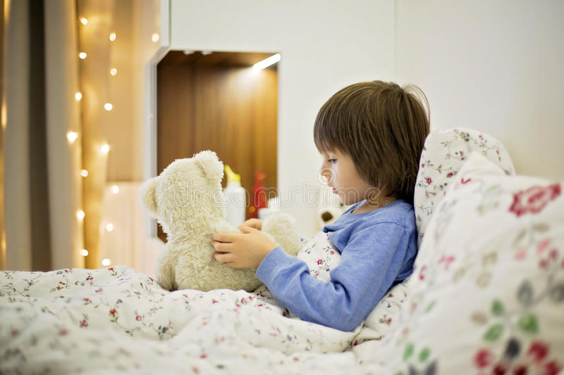 Cute sick child, boy, staying in bed, playing with teddy bear stock image