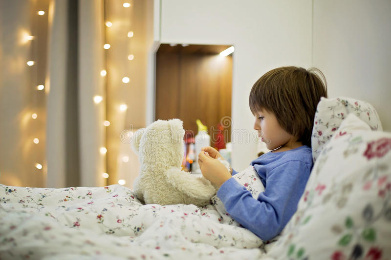 Cute sick child, boy, staying in bed, playing with teddy bear stock photos
