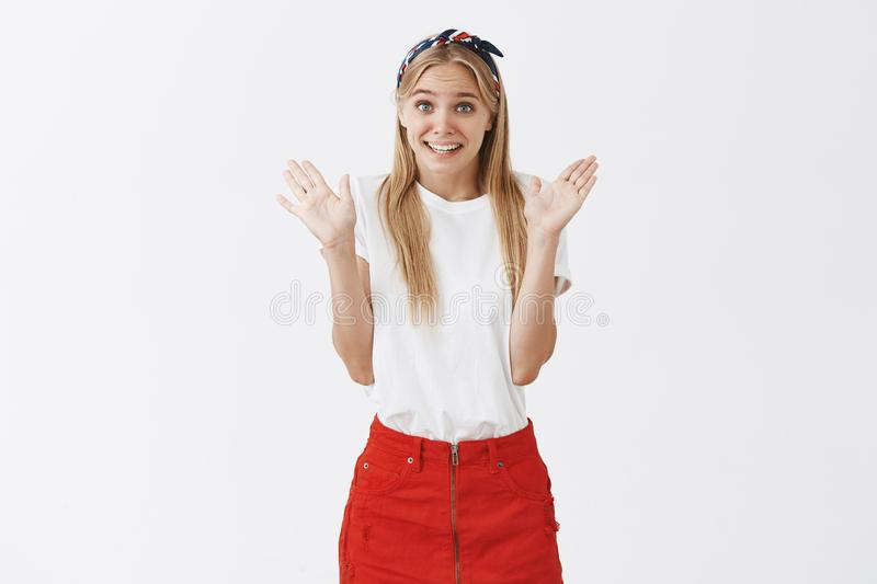 Cute silly caucasian girl with fair hair in stylish headband and red skirt, raising palms in surrender, frowning and stock photos