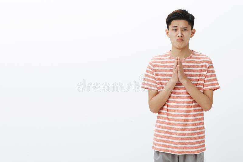 Cute silly guy sincerely asking forgiveness or permission, holding hands in pray over chest making cute gloomy. Expression while bagging for favour or help over royalty free stock photography