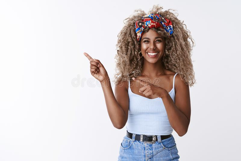 Cute sincere, friendly-looking blond curly-haired hipster woman with piercing, squinting joyfully, sharing cool link royalty free stock image