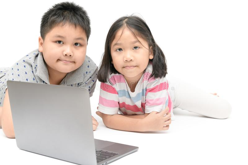 Cute sister and young brother play laptop isolated royalty free stock photography