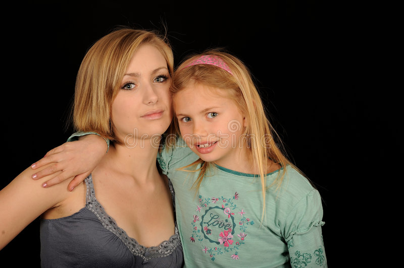 Cute Sisters. A portrait of a beautiful teenage girl with her cute little sister, on black studio background stock image