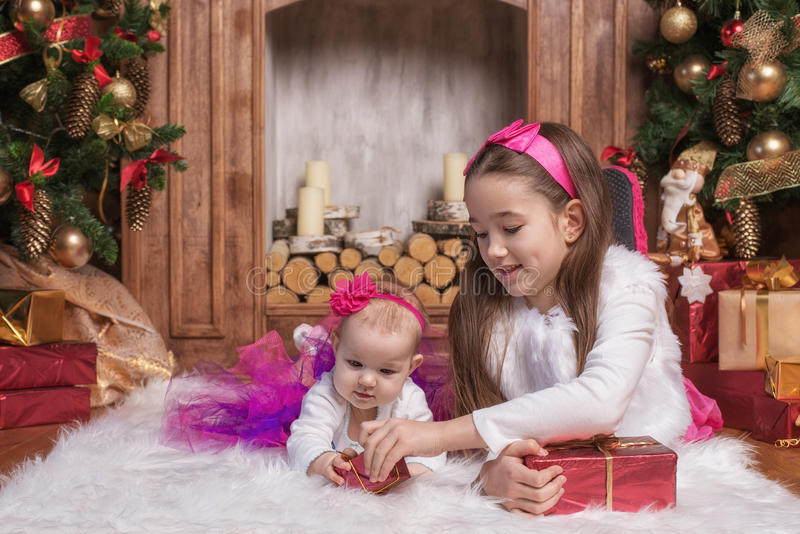 Cute sisters lying on white carpet near christmas trees, wearing pink skirts and red headbands. Smiling toddlers. Christmas royalty free stock images