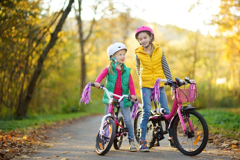 Cute sisters riding bikes in a city park on sunny autumn day. Active family leisure with kids. Children wearing safety hemet while royalty free stock photos