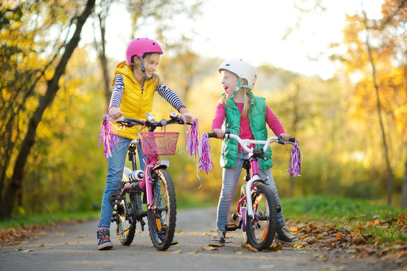 Cute sisters riding bikes in a city park on sunny autumn day. Active family leisure with kids. Children wearing safety hemet while royalty free stock images