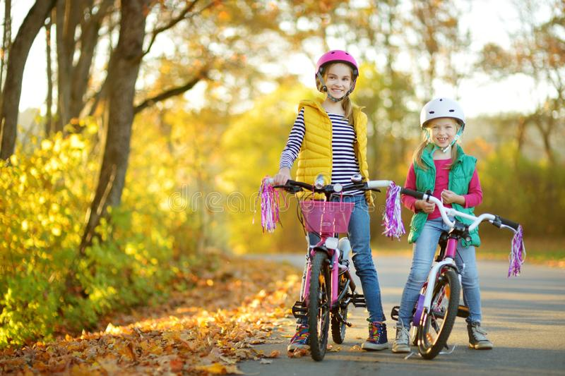 Cute sisters riding bikes in a city park on sunny autumn day. Active family leisure with kids. Children wearing safety hemet while. Cute little sisters riding stock photography