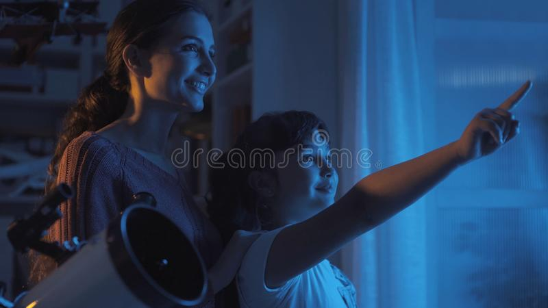 Cute sisters watching the stars with a telescope royalty free stock photos