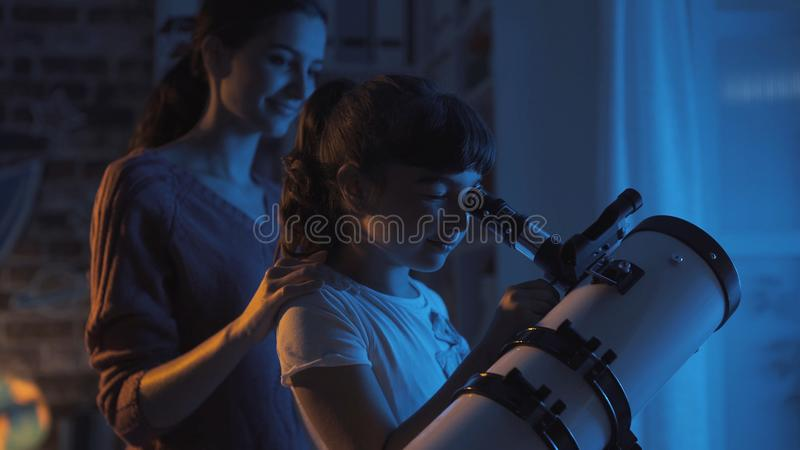 Cute sisters watching the stars with a telescope stock photography
