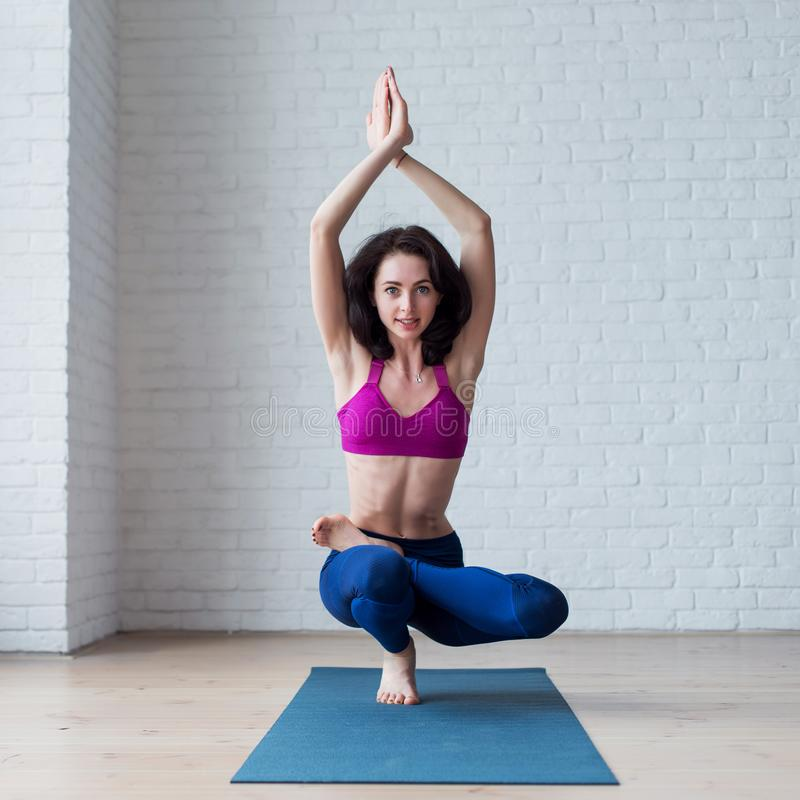Cute skinny young woman doing toe stand balance posture Padangustasana during yoga session.  stock images