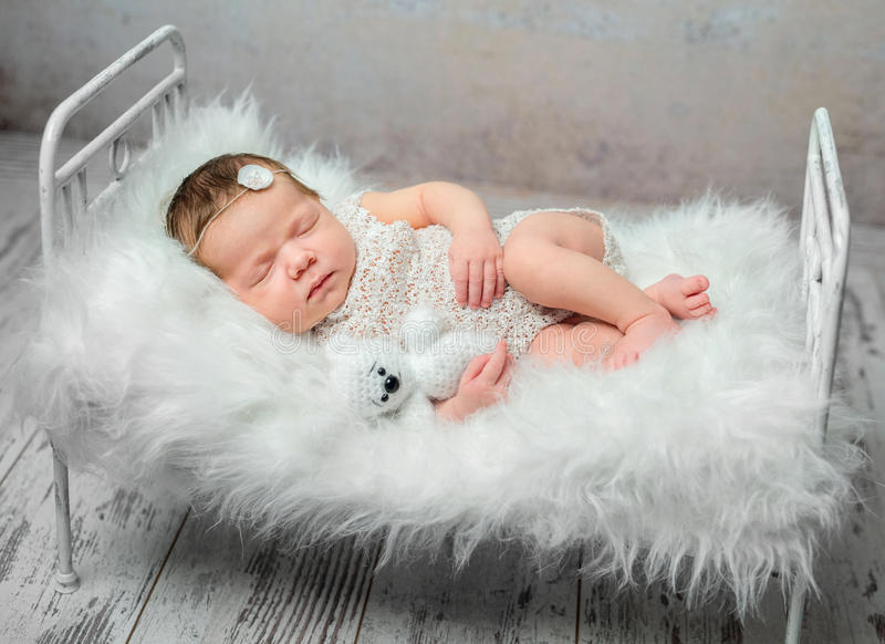 Cute sleeping newborn baby on cot with fluffy blanket royalty free stock photos