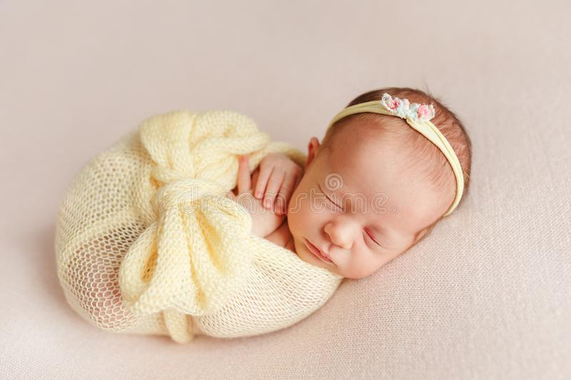 Cute sleeping newborn girl with a bandage on her head wrapped in stock photos
