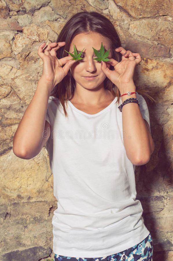 Cute slim female with illegal hemp leaves at her eyes stock photos