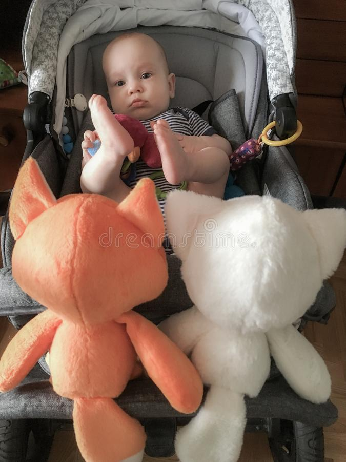 Cute small baby boy with a company of soft toys royalty free stock photography