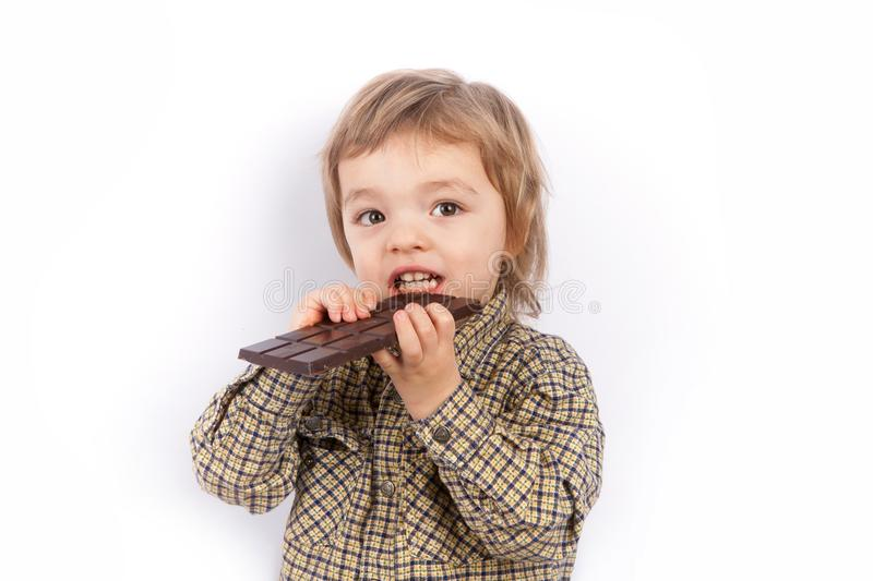 Cute small boy eating a chocolate bar stock photography