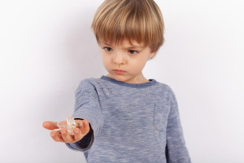 Cute small boy holding hearing aids on his palm. Focused on the hearing aid royalty free stock images