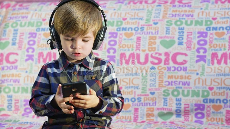 Cute small boy listening to the music in the black big headphones royalty free stock photo