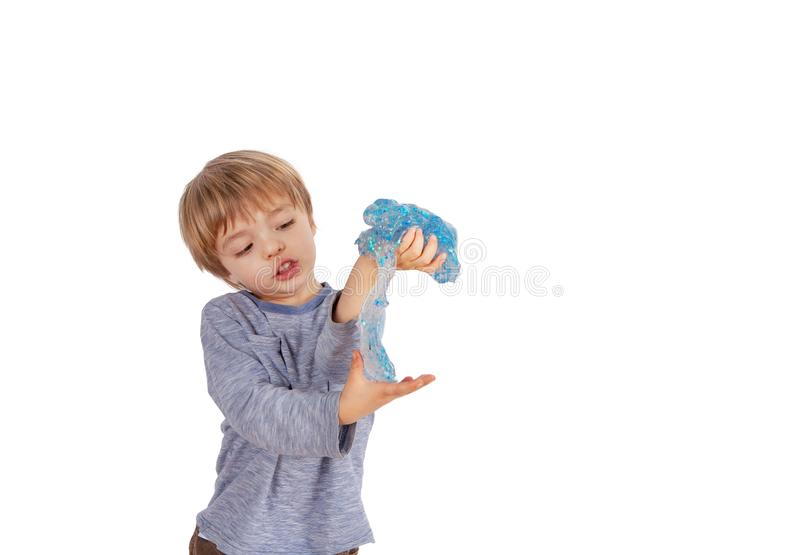 Cute small boy playing with glitter slime. Studio shot, isolated on white background stock photography