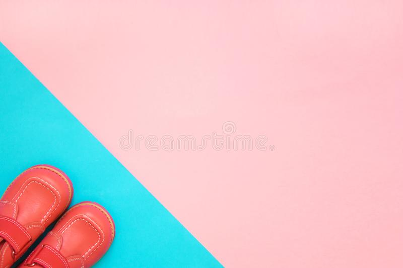 Small shoes fashionable living coral color on a bright background stock images