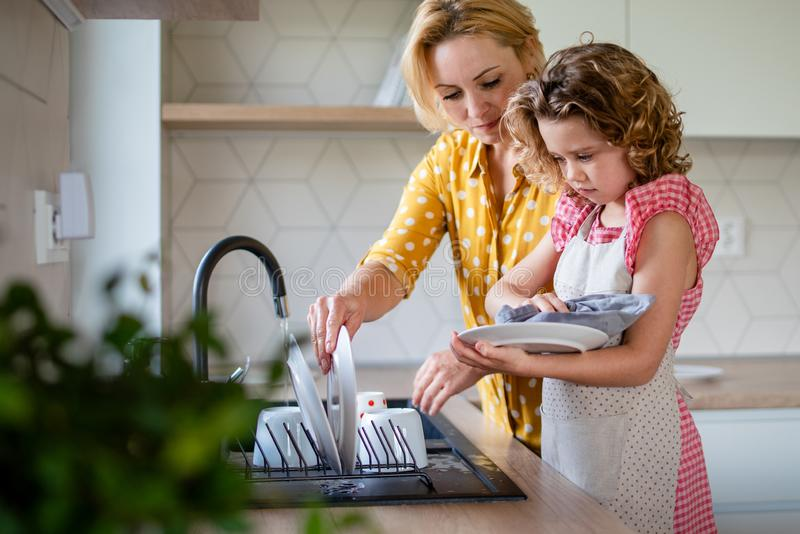 A cute small girl with mother indoors in kitchen at home, washing up dishes. A cute small girl with mother indoors in kitchen at home, washing up the dishes stock photography
