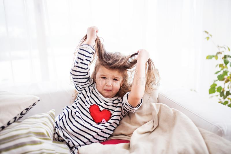 A small happy girl in striped T-shirt at home having fun. stock images