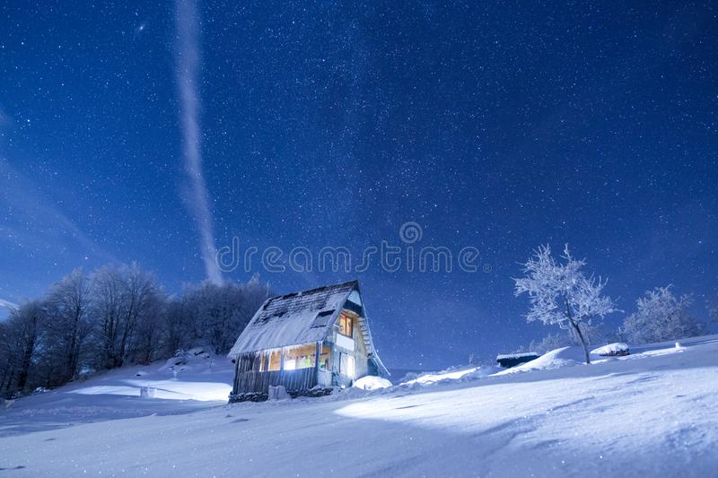 Frozen mountains cabin under a night sky filled with stars stock photos