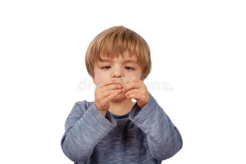 Cute small preschooler boy forming a heart shape from hearing aids stock photo