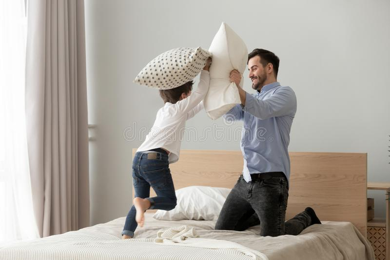Cute small son playing pillow fight on bed with father. Funny small kid son playing pillow fight with dad on bed, happy cute little child boy and young father stock photography