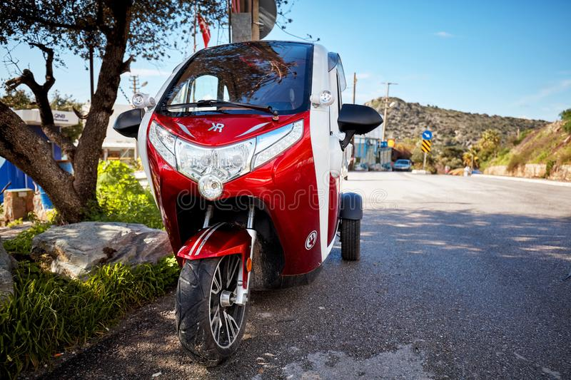 Cute small tricycle electric car parked near the asphalt road royalty free stock photos