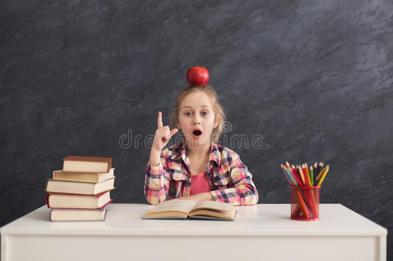 Cute smart girl raised hand while sitting at table stock image