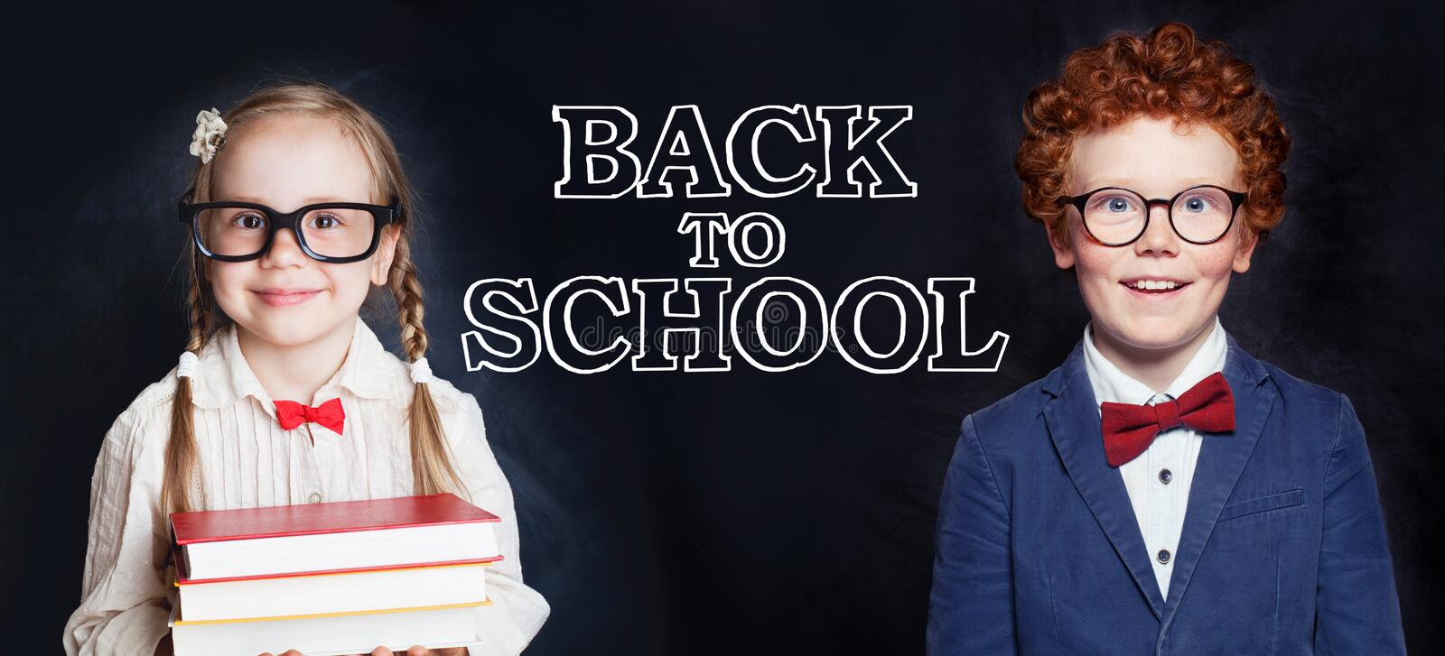 Cute smart kids boy and girl on blackboard background. Back to school concept stock image