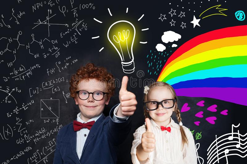 Cute smart kids showing thumb up against chalkboard background with light bulb, science formulas and arts pattern. royalty free stock image