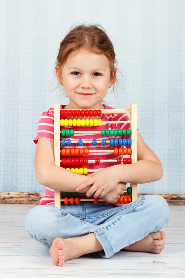 Cute and smart preschool girl holding abacus. Studio portrait of beautiful young girl royalty free stock photos