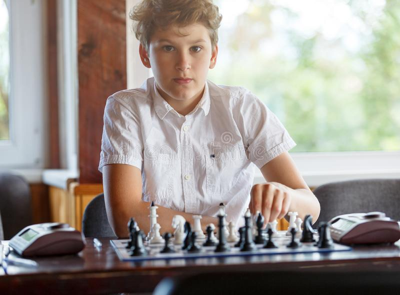 Cute, smart, 11 years old boy in white shirt sits in the classroom and plays chess on the chessboard. Training, lesson, hobby stock photography