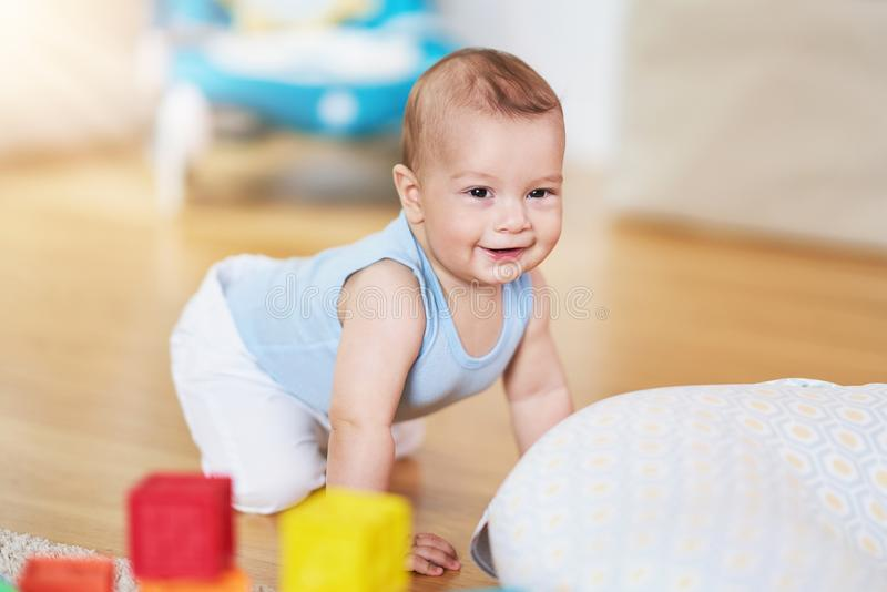 Cute smiling baby boy crawling on floor in living room royalty free stock images