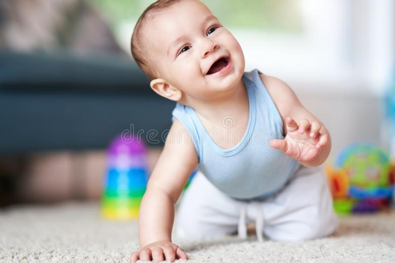 Cute smiling baby boy crawling on floor in living room royalty free stock photo