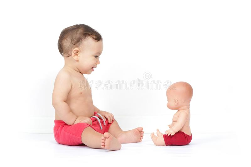 Cute smiling baby boy looks at doll similar to him royalty free stock image