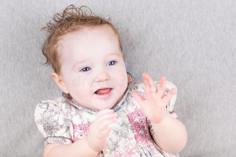 Cute smiling baby girl clapping hands stock photo