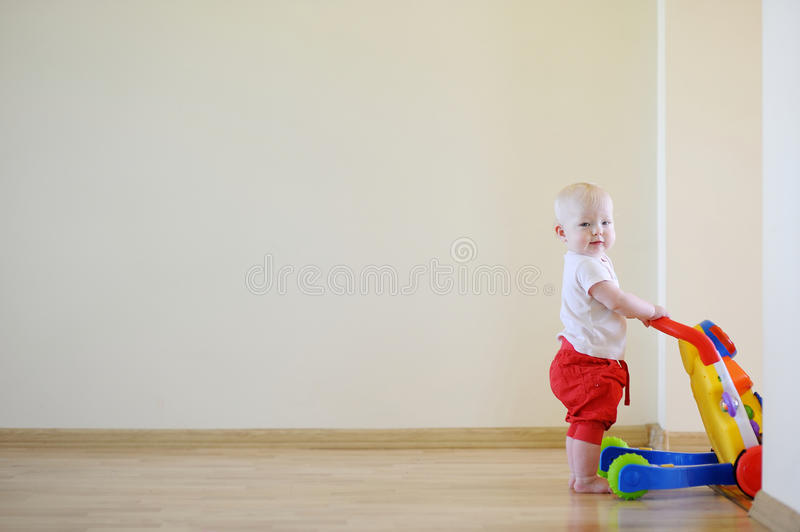 Cute smiling baby girl with toy walker royalty free stock photos