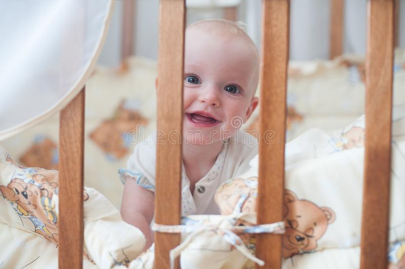 Cute smiling baby looking out of the crib. Funny kid in bed. Cute smiling baby looking out of the crib. Funny kid in bed stock photos