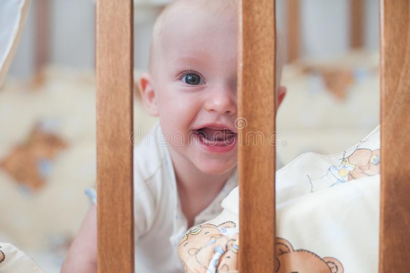 Cute laughing baby looking out of the crib. Funny kid in bed. Close up portrait. Cute smiling baby looking out of the crib. Funny kid in bed royalty free stock image